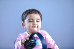 Gullig indisk/asiatisk liten flicka som lyssnar till musik på hörlurar arkivbild