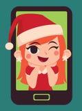 Gullig julflicka inom en telefon Arkivbild