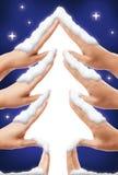 Gullig julgranform som göras av händer som täckas med vit snö på blå stjärnklar himmelbakgrund royaltyfria foton