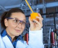 Gullig kemist som fungerar i laboratorium Arkivbild