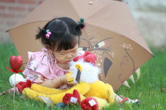 Gullig kines behandla som ett barn den flotta leksaken för flickalek på gräsmattan Royaltyfria Foton