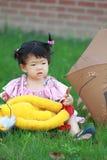 Gullig kines behandla som ett barn den flotta leksaken för flickalek på gräsmattan Royaltyfri Foto