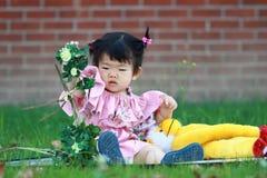 Gullig kines behandla som ett barn den flotta leksaken för flickalek på gräsmattan Royaltyfri Bild
