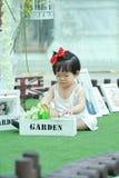 Gullig kines behandla som ett barn flickalekblommor i en trädgård royaltyfria foton