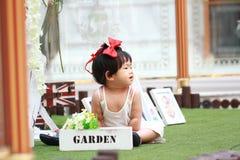 Gullig kines behandla som ett barn flickalekblommor i en trädgård royaltyfri foto
