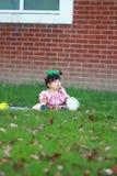 Gullig kines behandla som ett barn flickan bär exponeringsglas på gräsmattan Arkivbild
