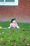 Gullig kines behandla som ett barn flickan bär exponeringsglas på gräsmattan Royaltyfria Bilder