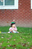 Gullig kines behandla som ett barn flickan bär exponeringsglas på gräsmattan Royaltyfri Foto