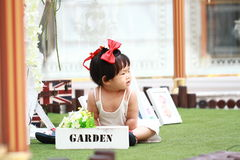 Gullig kines behandla som ett barn flickan i röd pilbåge på head lek i en trädgård Royaltyfri Foto