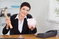 Gullig kontorsarbetare som bryter en piggybank Arkivfoton