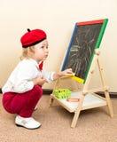 Gullig krita för barnflickateckning på staffli i dräkt av konstnären i dagis Royaltyfri Foto