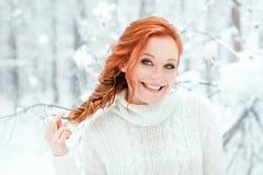 Gullig kvinna i den vita tröjan i snöig skog Fotografering för Bildbyråer