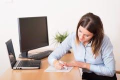 Gullig kvinna i kontoret Arkivfoto