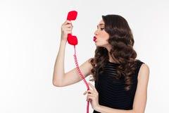 Gullig kvinna i retro stil som överför kyssen in i telefonmottagaren Arkivfoton