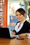 Gullig kvinna med bärbar dator och anteckningsboken Royaltyfri Bild