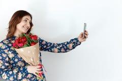 Gullig kvinna med gruppen av tulpan och mobiltelefonen Arkivfoto