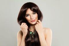Gullig kvinna med långt brunt silkeslent hår och makeup på bakgrund royaltyfria bilder