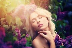 Gullig kvinna med sommarljus- och lilablommor royaltyfri foto