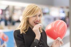 Gullig kvinna som äter en choklad royaltyfria bilder