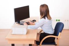Gullig kvinna som arbetar i kontoret Arkivfoton