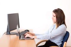 Gullig kvinna som arbetar på anteckningsboken i kontoret Royaltyfria Bilder