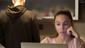 Gullig kvinna som arbetar på bärbara datorn i köket medan hennes pojkvänanseende som gör hennes coffe eller te Att sätta för man  royaltyfri foto