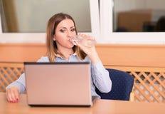 Gullig kvinna som dricker ett vatten i kontoret Arkivfoton