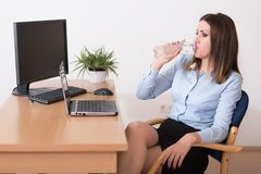 Gullig kvinna som dricker ett vatten i kontoret Arkivbilder