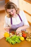 Gullig kvinna som förbereder fisken i kök royaltyfria foton