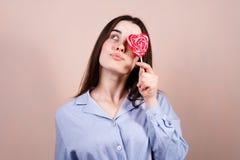 Gullig kvinna som har gyckel med den hj?rta formade klubban royaltyfri fotografi
