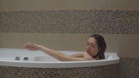 Gullig kvinna som kopplar av i badrummet arkivfilmer
