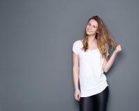 Gullig kvinna som ler med handen i hår Fotografering för Bildbyråer