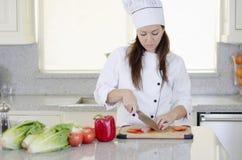 Gullig kvinnlig kock som gör en sallad Arkivfoton