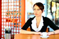 Gullig kvinnlig på det dricka kaffet för cafe Royaltyfria Bilder