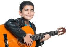 Gullig latinamerikansk pojke som spelar en akustisk gitarr Royaltyfri Bild