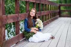 Gullig le flicka med en bukett av tusenskönor på barfota drömma för pir Arkivbild