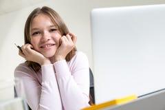 Gullig le flicka på skrivbordet Arkivfoto