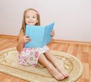Gullig le liten flicka som läser en bok royaltyfria foton