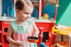 Gullig le litet barnflicka som hemma spelar med leksakkök Royaltyfria Bilder