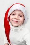 Gullig le pojke i hatt av jultomten Royaltyfria Bilder