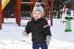 Gullig le pojke som spelar med snö arkivbilder