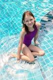Gullig le preteen flicka som sitter på simbassängkanten Lopp semester, barndom arkivfoton