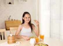Gullig le preteenflicka som har den sunda frukosten: avokadosmörgås och orange fruktsaft Sunt livsstilbegrepp, vegetarisk mat fotografering för bildbyråer