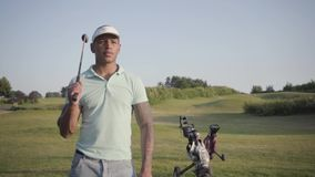 Gullig le säker lyckad mitt för stående - östlig man med ett golfklubbanseende på en golfbana i bra soligt lager videofilmer