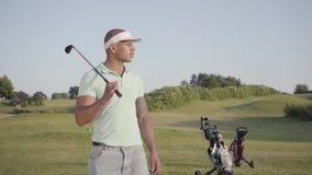 Gullig le säker lyckad mitt för stående - östlig man med ett golfklubbanseende på en golfbana i bra soligt stock video