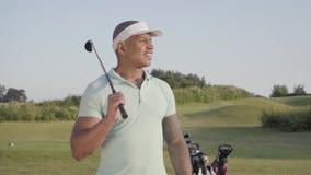 Gullig le säker lyckad mitt för stående - östlig man med ett golfklubbanseende på en golfbana i bra soligt arkivfilmer