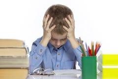 Gullig ledsen skolpojke som sitter på tabellen med böcker och anteckningsböcker Tröttat av att göra läxa bakgrund isolerad white arkivbilder