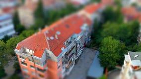 Gullig leksak som det miniatyrlutande-förskjutning effektfotoet av det röda keramiska belägga med tegel taket av en bostads- bygg arkivfoton