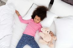 Gullig liten afrikansk amerikanflicka med att sova för nallebjörn arkivfoto