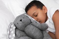 Gullig liten afrikansk amerikanpojke med att sova för leksakkanin fotografering för bildbyråer